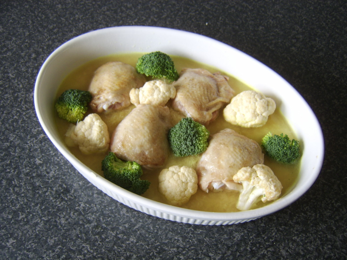 Broccoli and cauliflower florets are interspersed between the chicken thighs