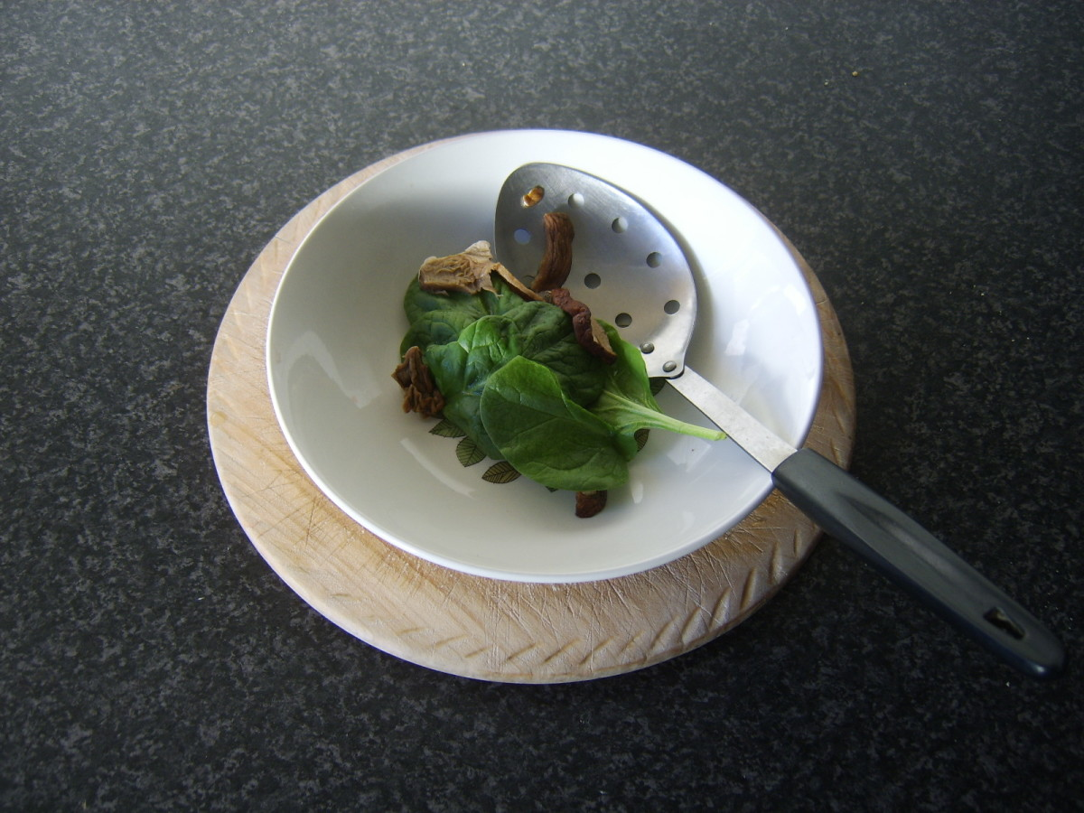 Porcini mushrooms and spinach are removed from water with a slotted spoon