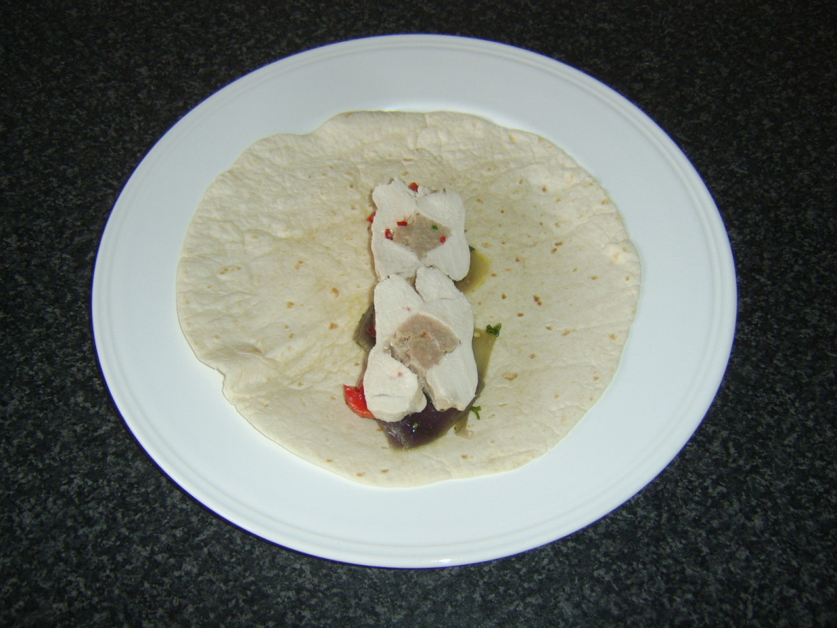 Chicken breasts are stuffed with a spicy pork mixture, casseroled then sliced and served in tortilla wraps with spicy vegetables and condiments