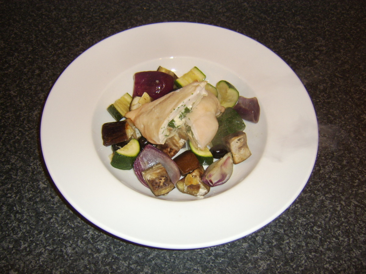 Stuffed chicken breast is served on a bed of roasted Mediterranean vegetables