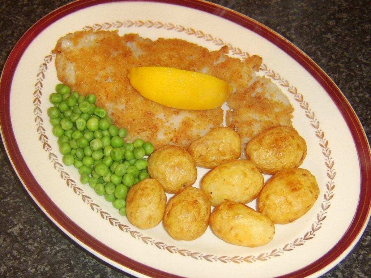 Breaded fried pollack fillet with roast potatoes and peas