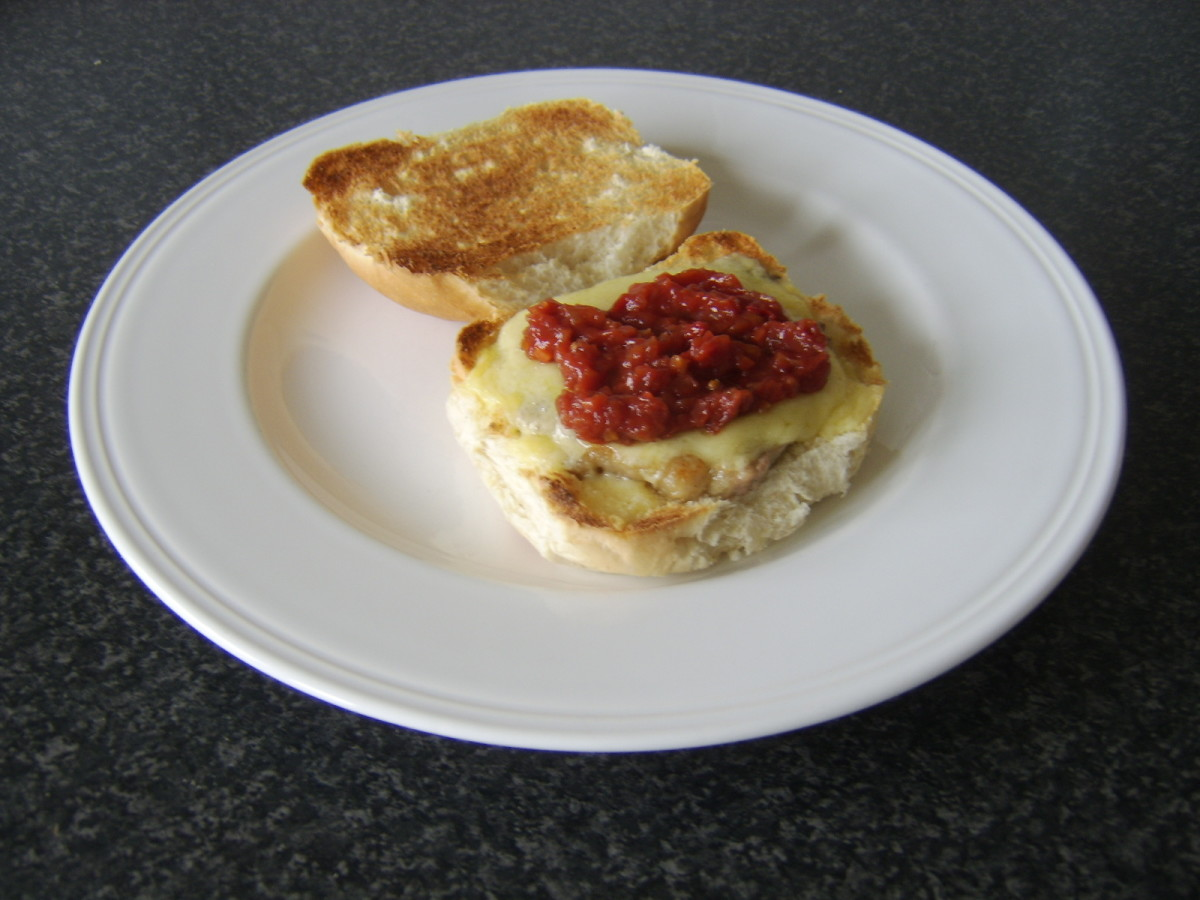Cheddar cheese melted over steak with spicy tomato relish on a bread roll