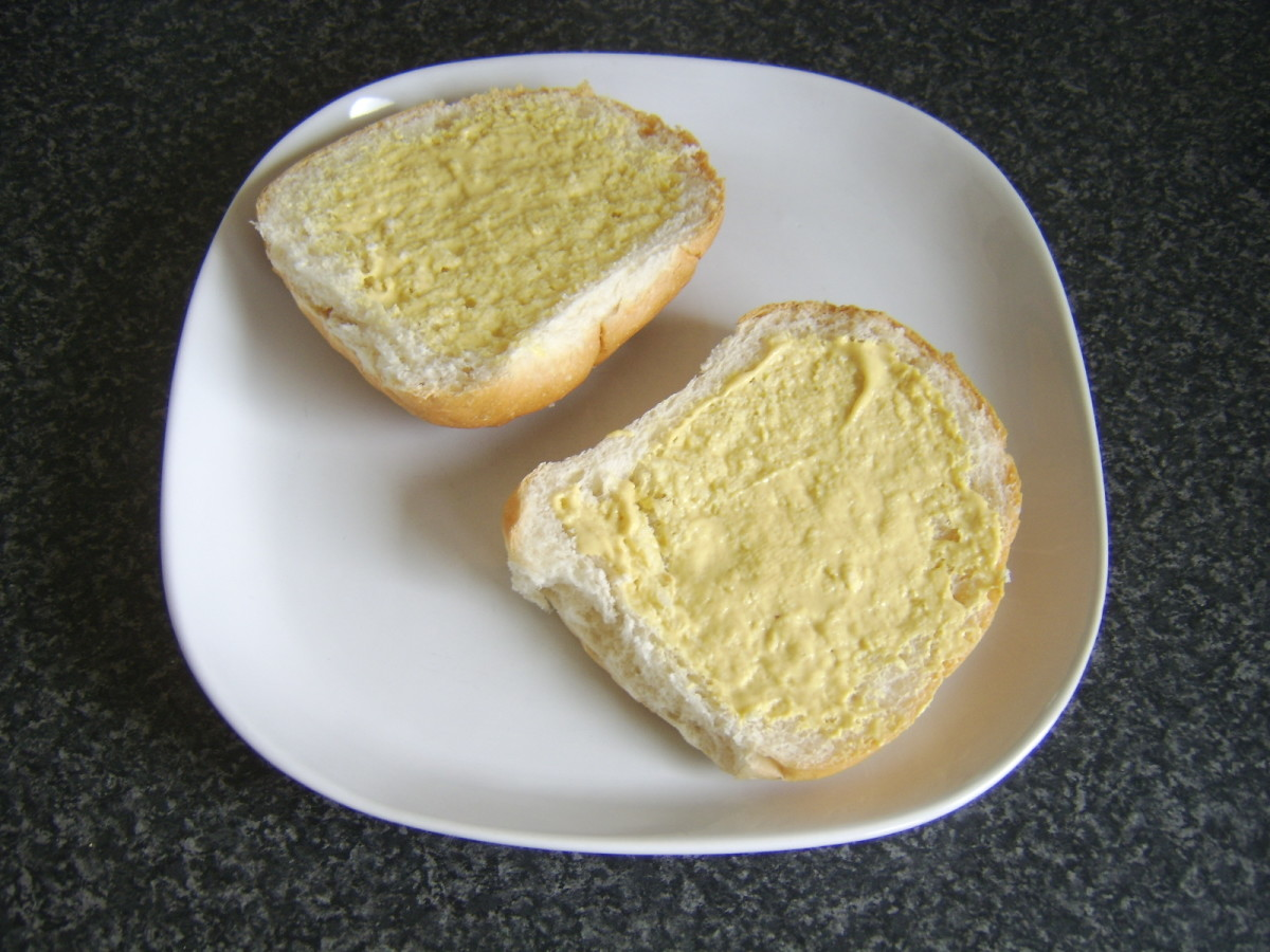 Bread roll is spread with Dijon mustard