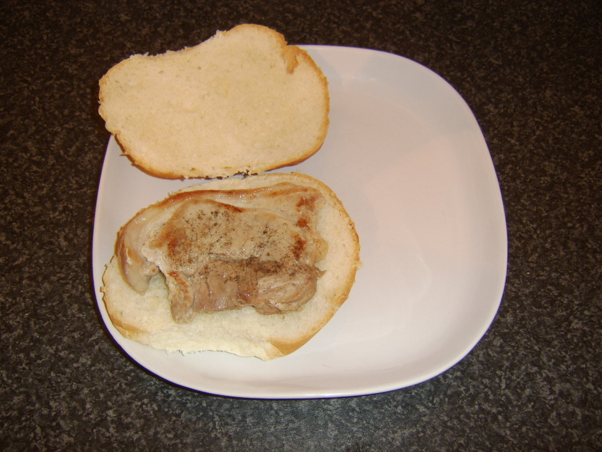 Pork leg steak is laid on bread roll