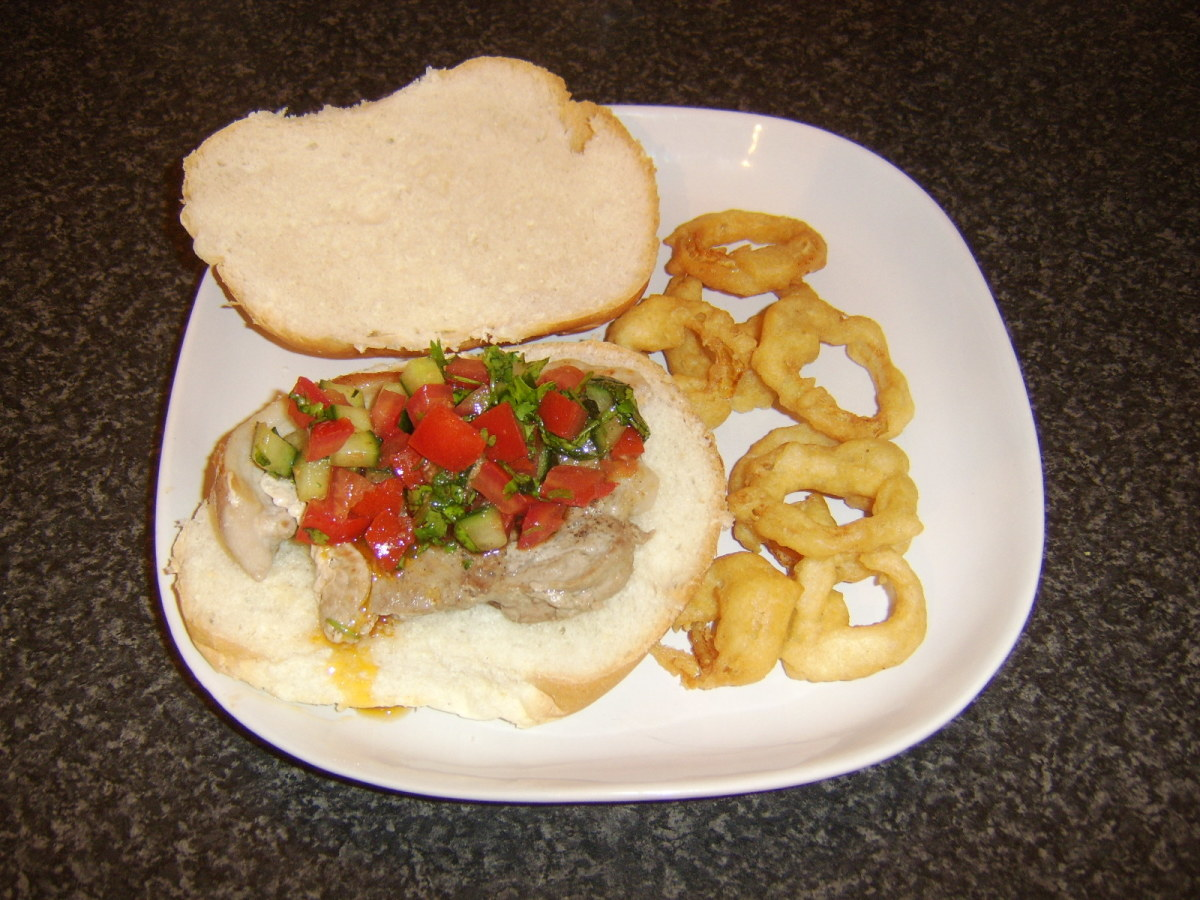 Leg of pork steak and salsa sandwich with homemade onion rings