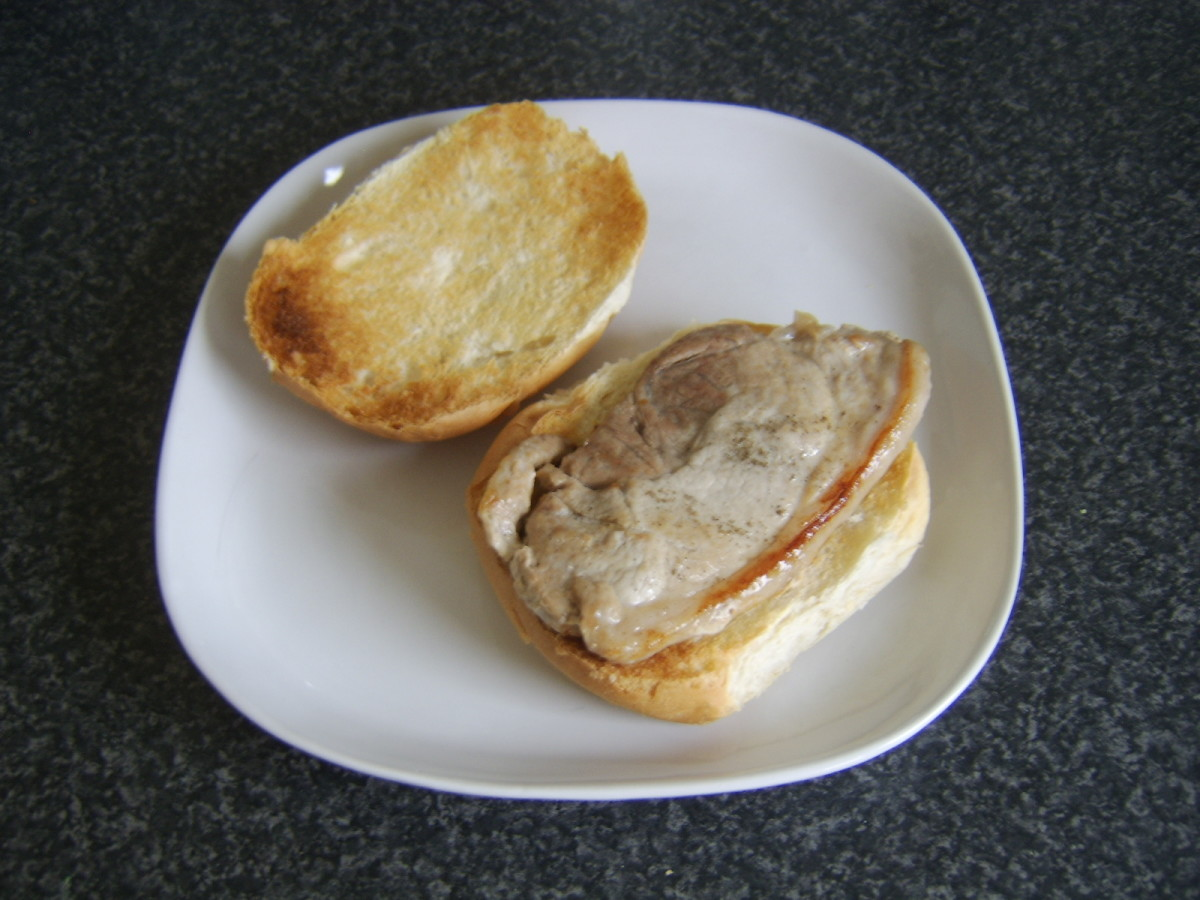 Rested leg of pork steak is laid on bread roll