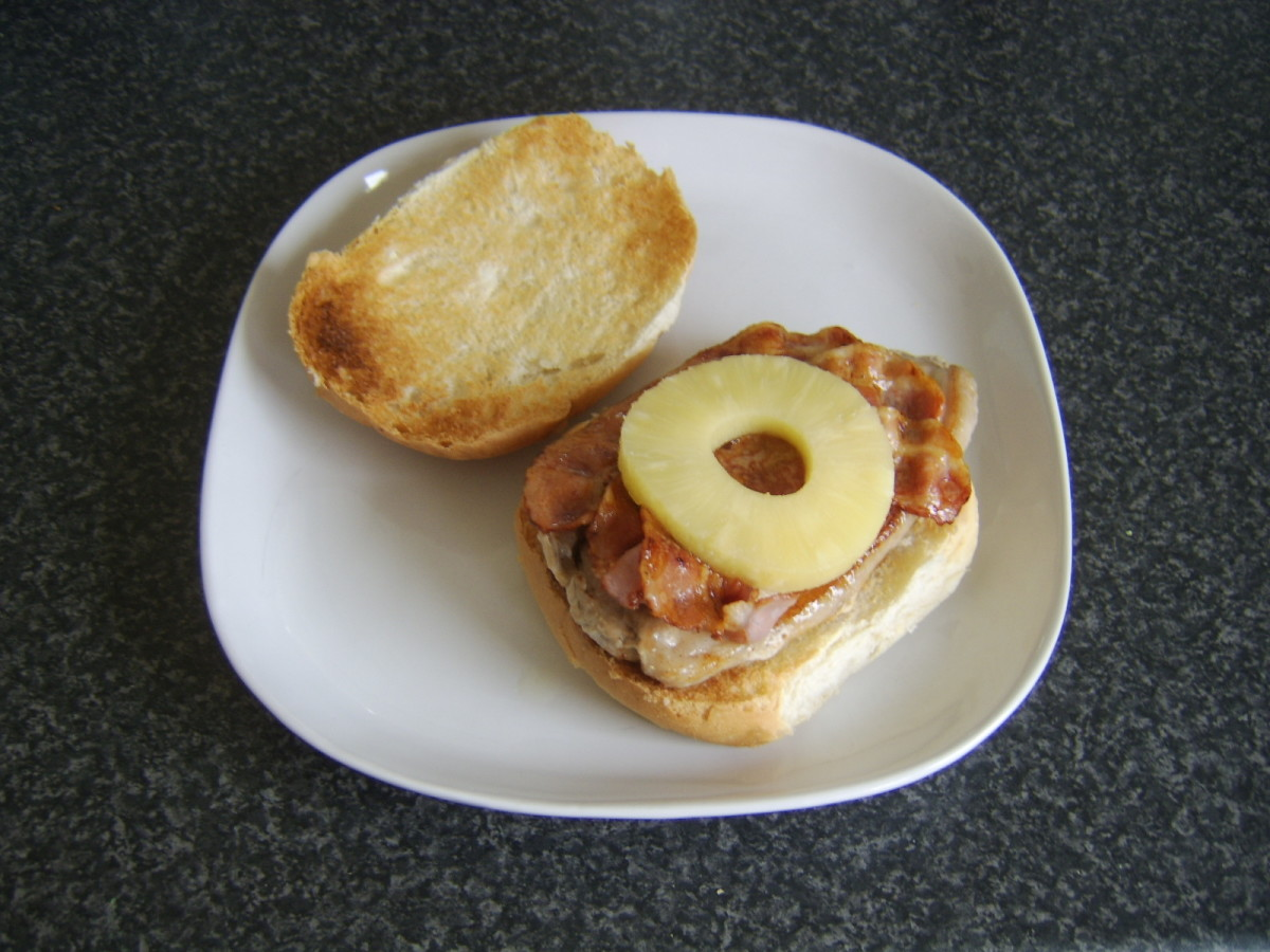 Pineapple ring is laid on bacon and pork steak