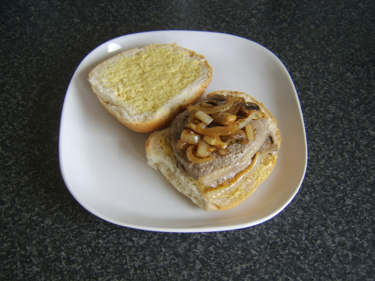 Burger style steak sandwich with mustard, mushrooms and onions