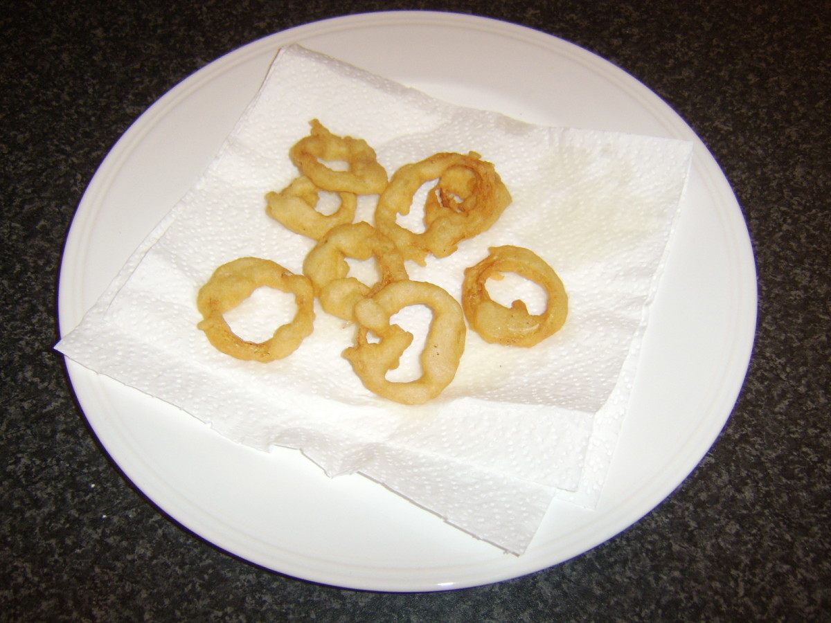 Onion rings are drained on kitchen paper