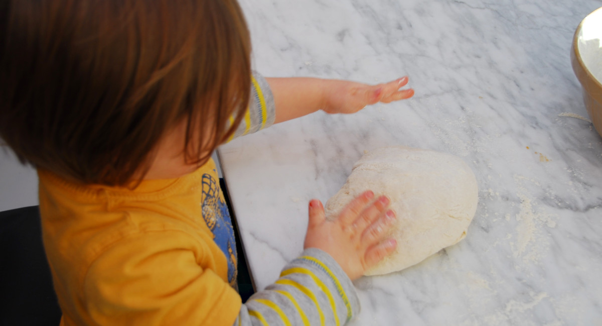Patting the dough and getting a feel for the dough.