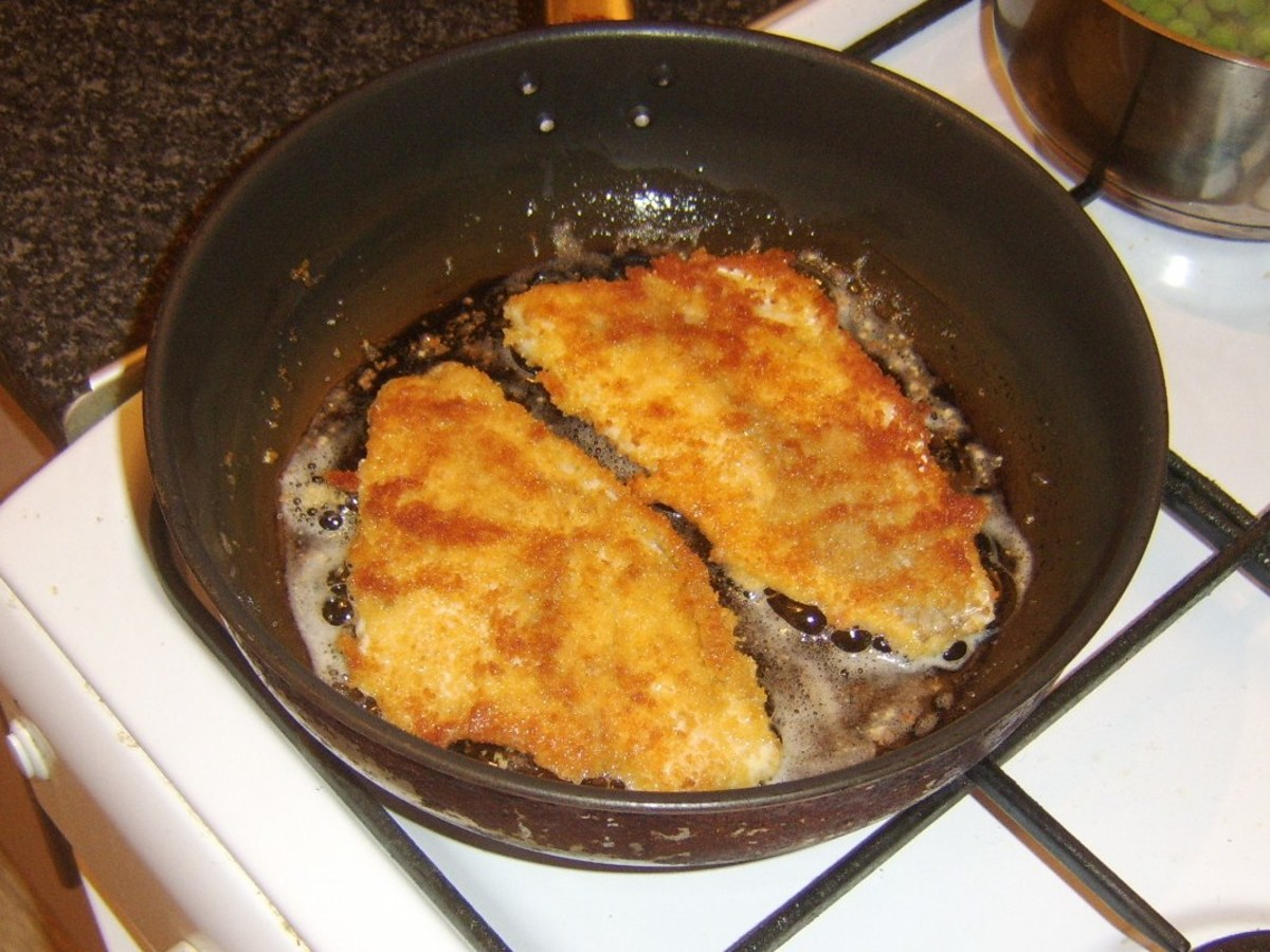 Breaded sea bream fillets are turned in frying pan