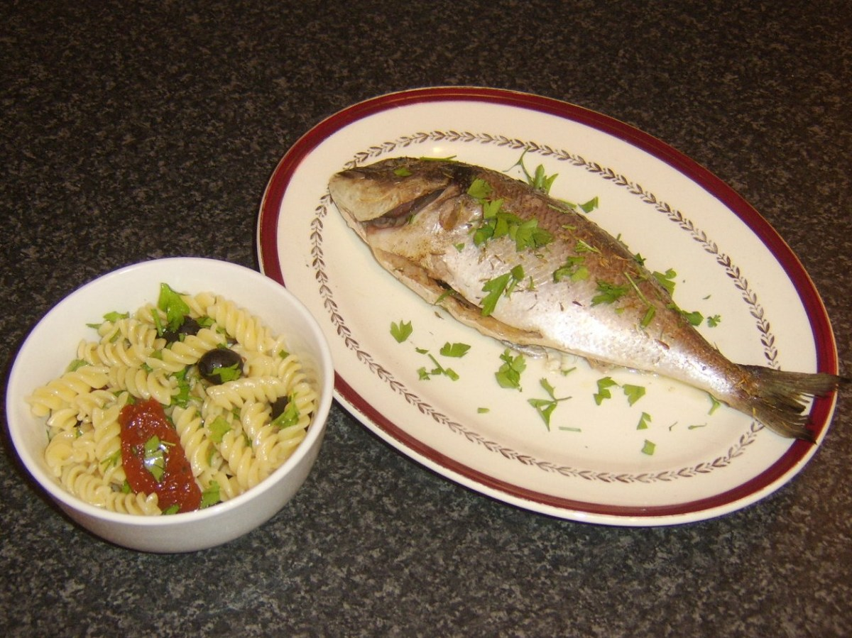 Oven baked whole sea bream served wimply with some fusilli pasta, sun dried tomatoes in olive oil and black olives