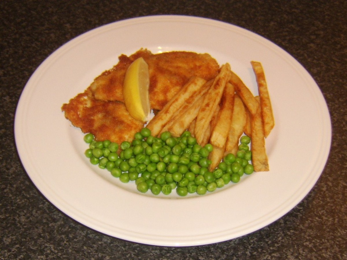 Sea bream fillets simply fried in breadcrumbs and served with chips and peas