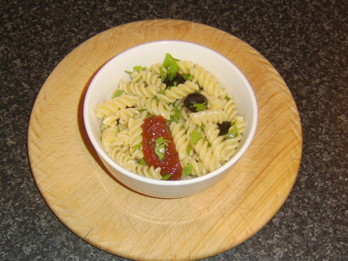 Fusilli pasta is spooned in to a small serving bowl