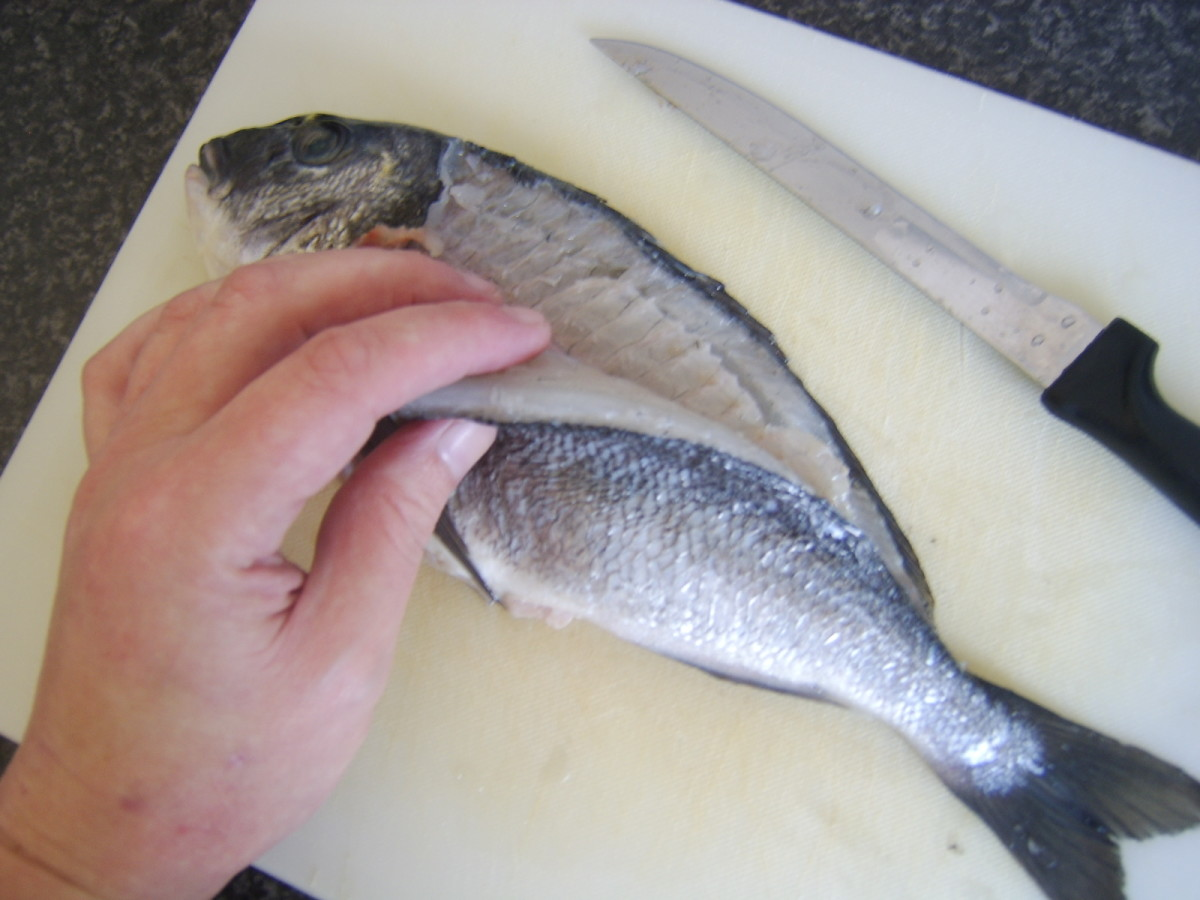 Removing the first fillet from the sea bream