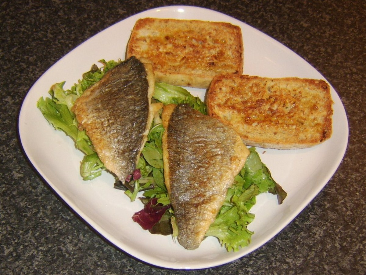 Pan fried sea bream fillets on a simple leafy salad with bruschetta