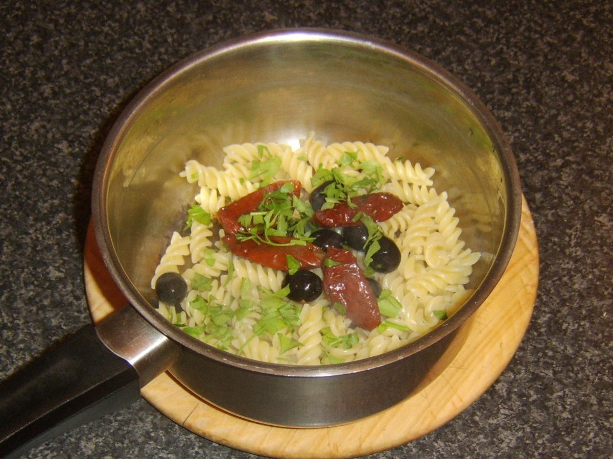 Sun dried tomatoes, olives and parsley are added to fusilli pasta