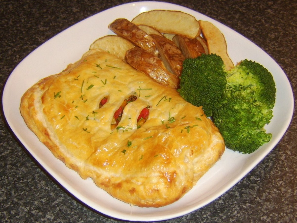 Potato wedges and broccoli are plated with gammon steak en croute