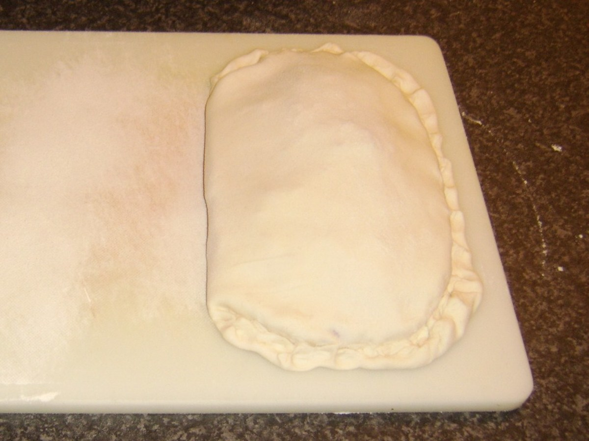 Pastry is folded over gammon steak and filling before being crimped around the edges