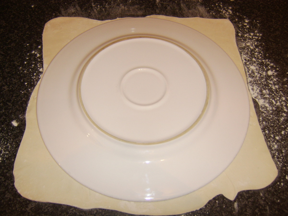 A large dinner plate is used as a template to cut a circle from the rolled pastry