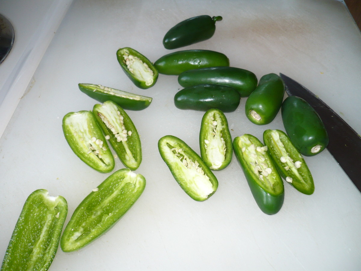 Wear gloves and slice the jalapeno peppers in half. Then remove most of the seeds. I leave some seeds in because I love the heat.