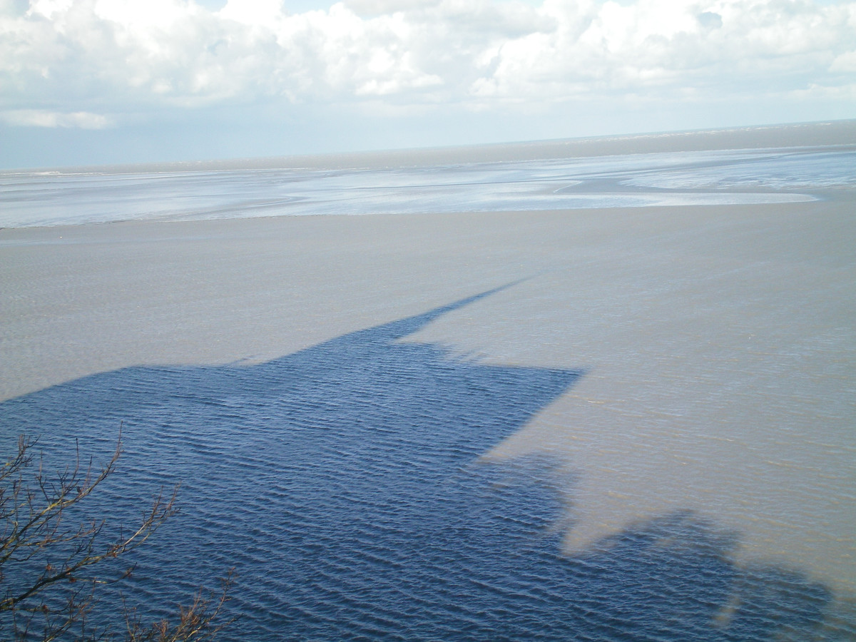 The shadow of Mont St Michel Abbé on the rising tide (c). A.Harrison