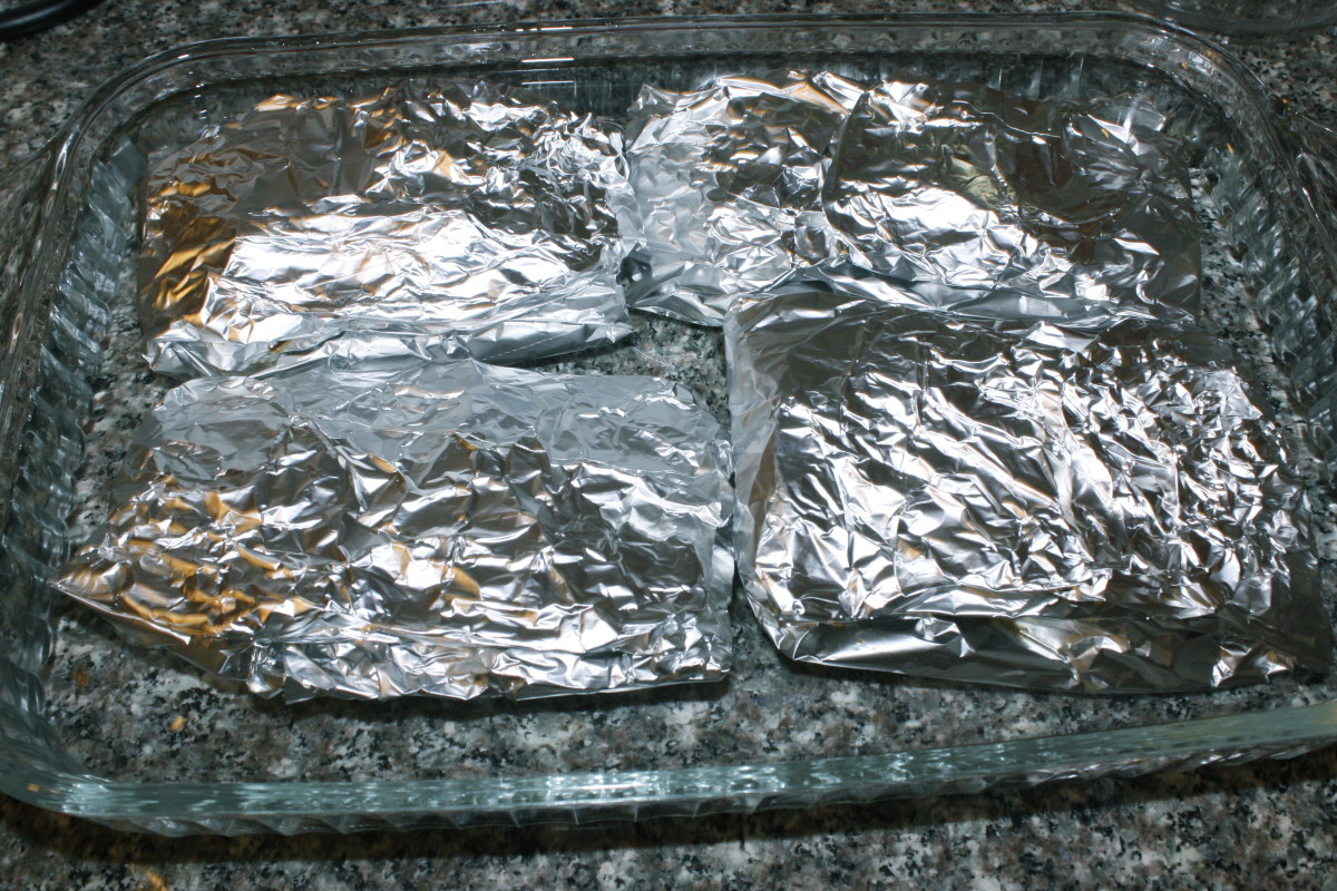 Foil packets inside of the water ready to be placed in the oven.