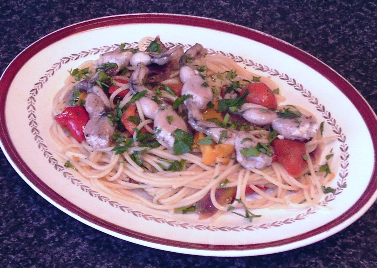 Sauteed frogs' legs on a bed of spaghetti and roasted vegetables