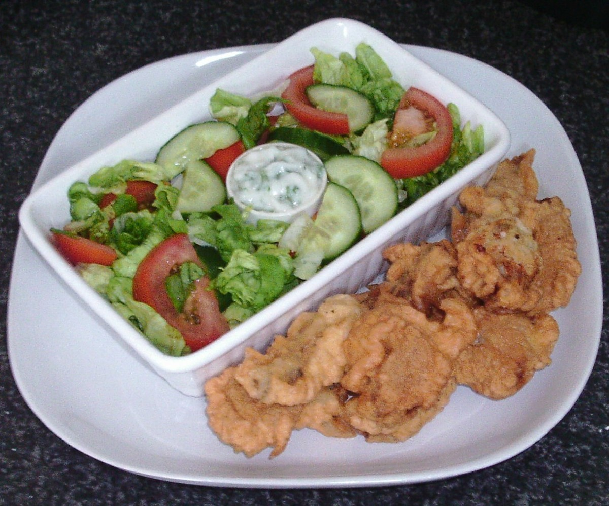 Deep fried frogs' legs in batter are served with a simple salad and garlic mayo dip