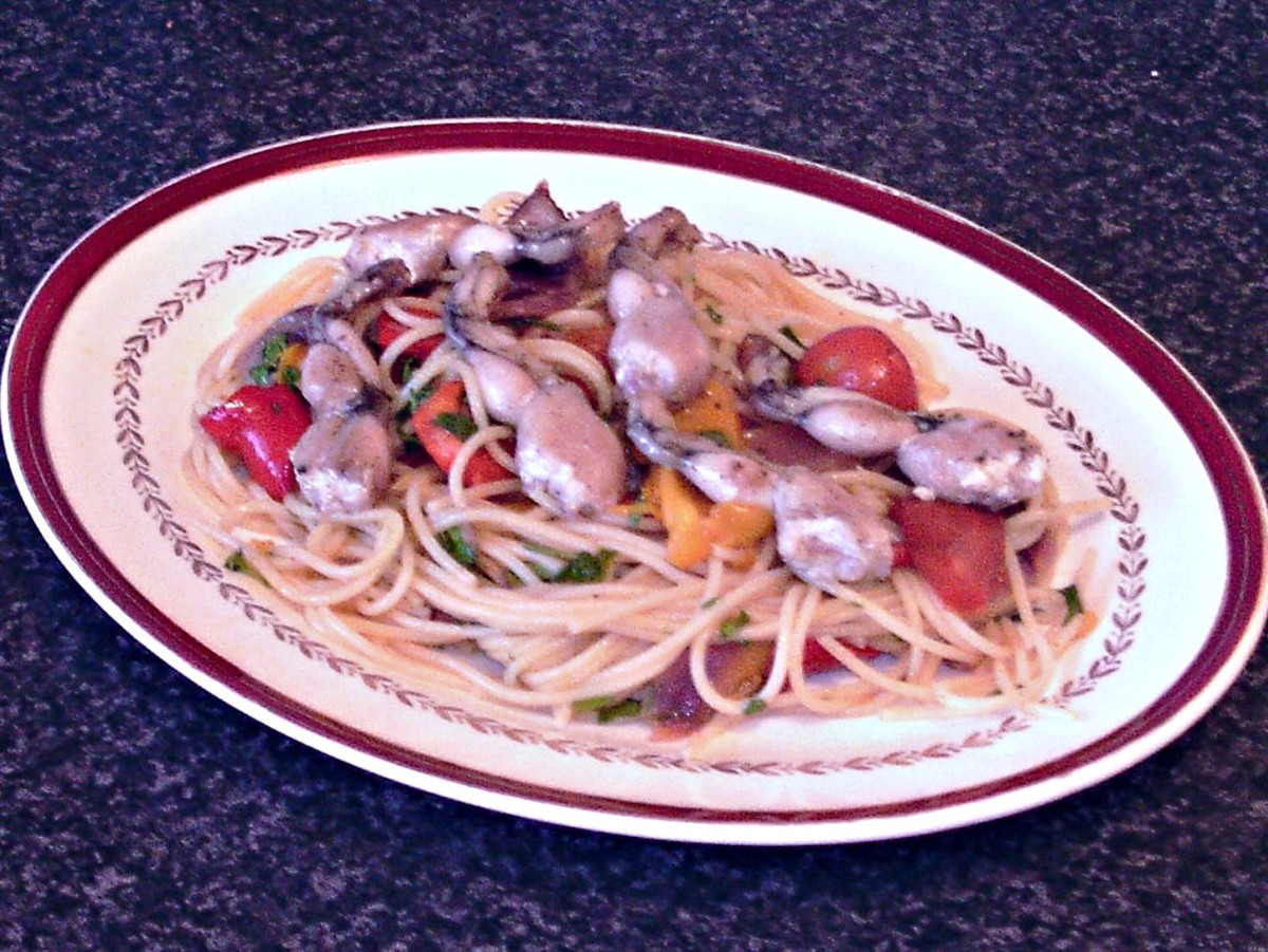 Spaghetti and vegetables are plated with frogs' legs on top
