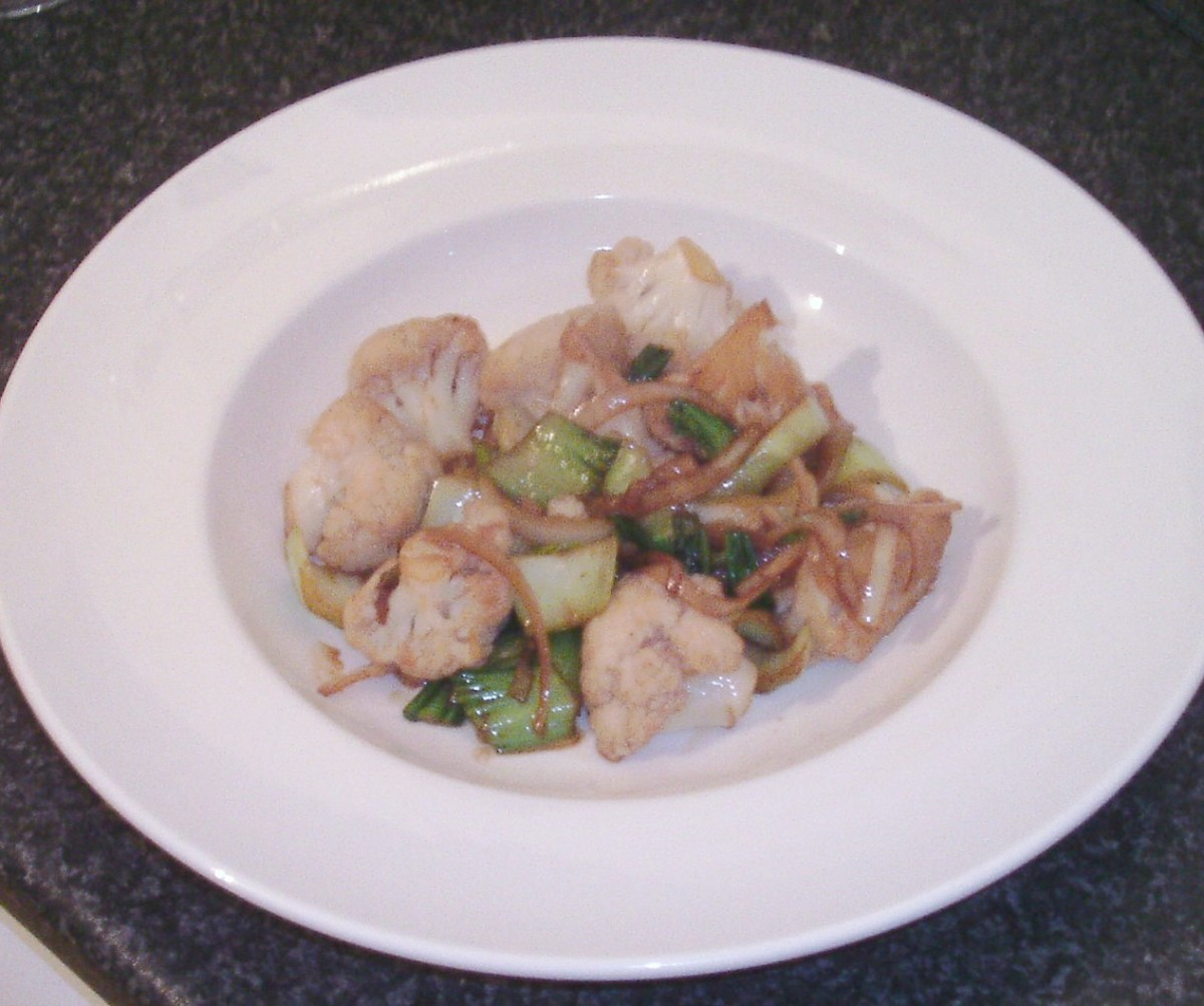 Sauteed cauliflower and pak choi are plated
