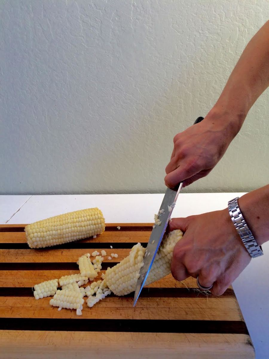 Use a knife to scrape the kernels from the cob. Be sure to watch your fingers and scrape downward toward the cutting board.