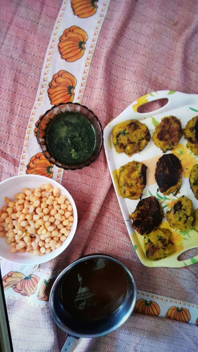 All ingredients for the aloo tikki chaat preparation are ready. The green chutney consists of coriander-chilly paste while the brown chutney is the tamarind-jaggery paste. Don't mind the black tikkis!