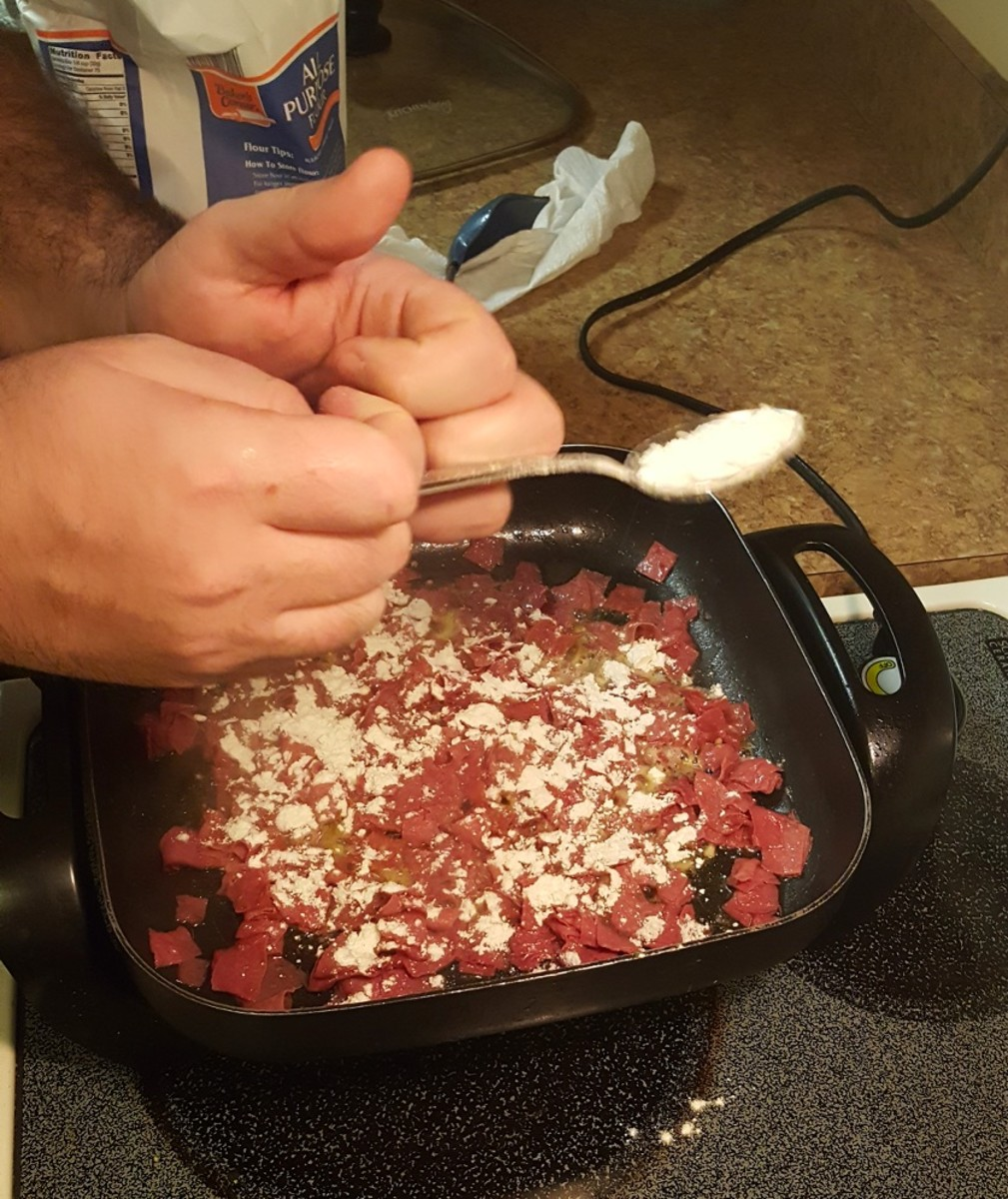 Gently tap a tablespoon to sprinkle flour on top of beef.