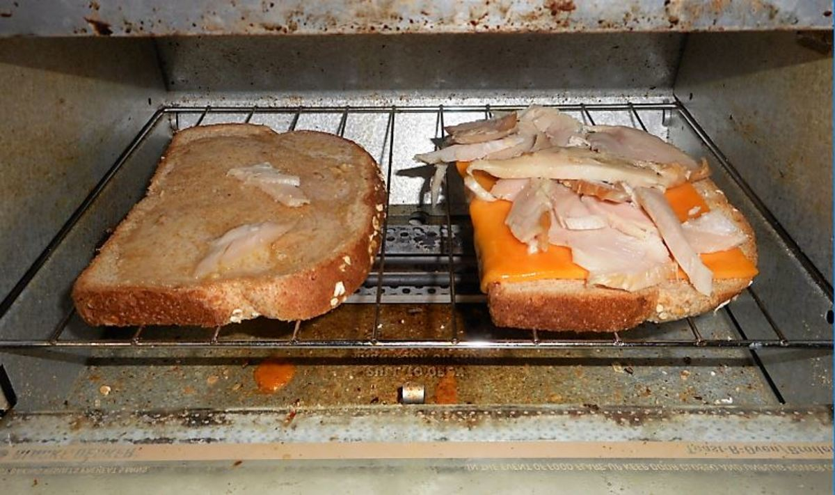 The buttered slice and cheese and turkey slice in the toaster oven.