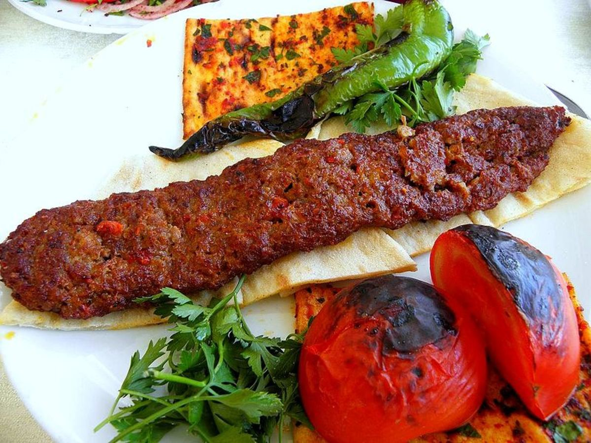 Kebab served with khubz, roasted tomatoes and capsicum and parsley.