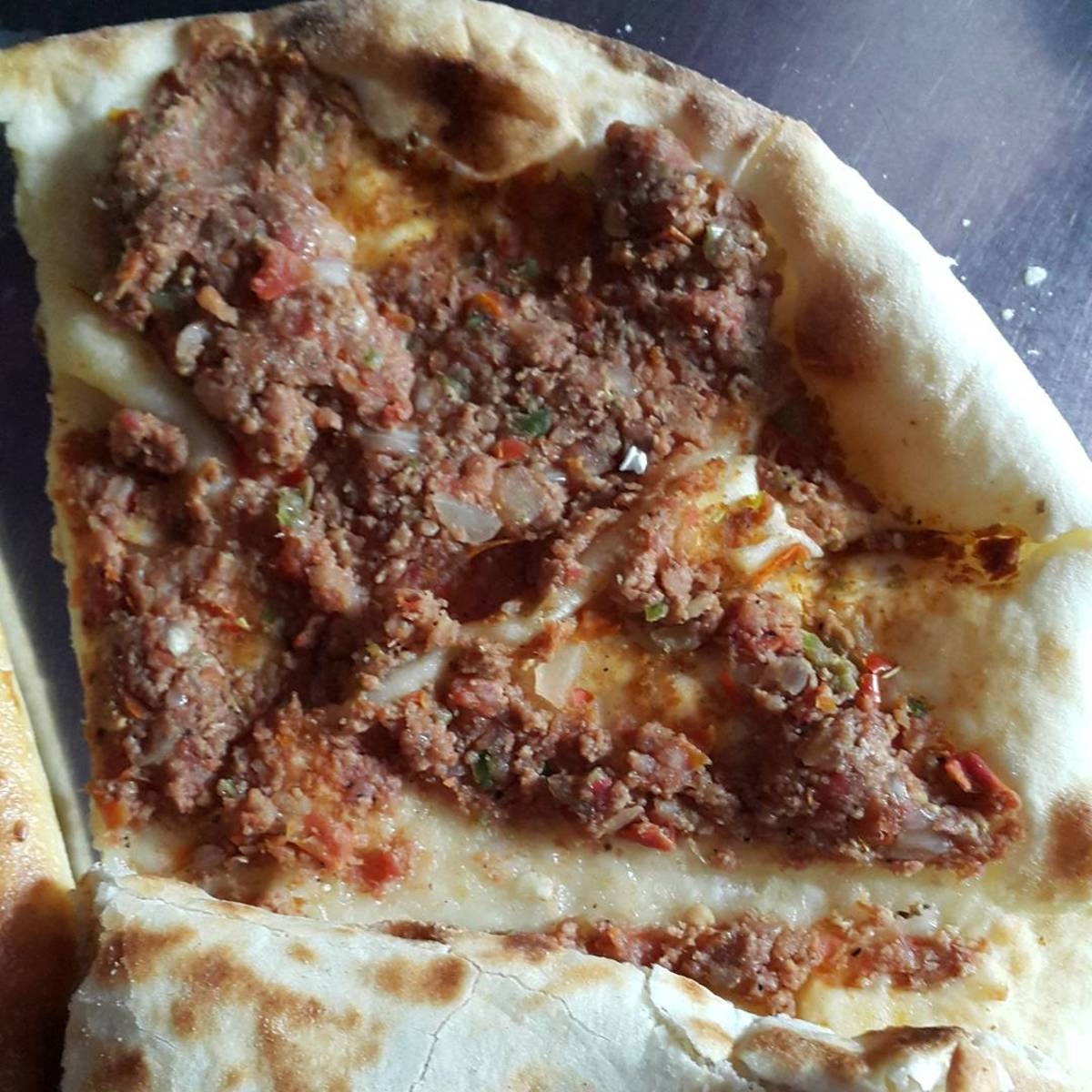 Fatayer Laham is a pizza like crust topped with minced meat.