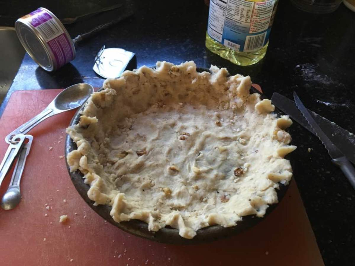 The pie crust, after being worked to cover the pie dish and its edges fluted.