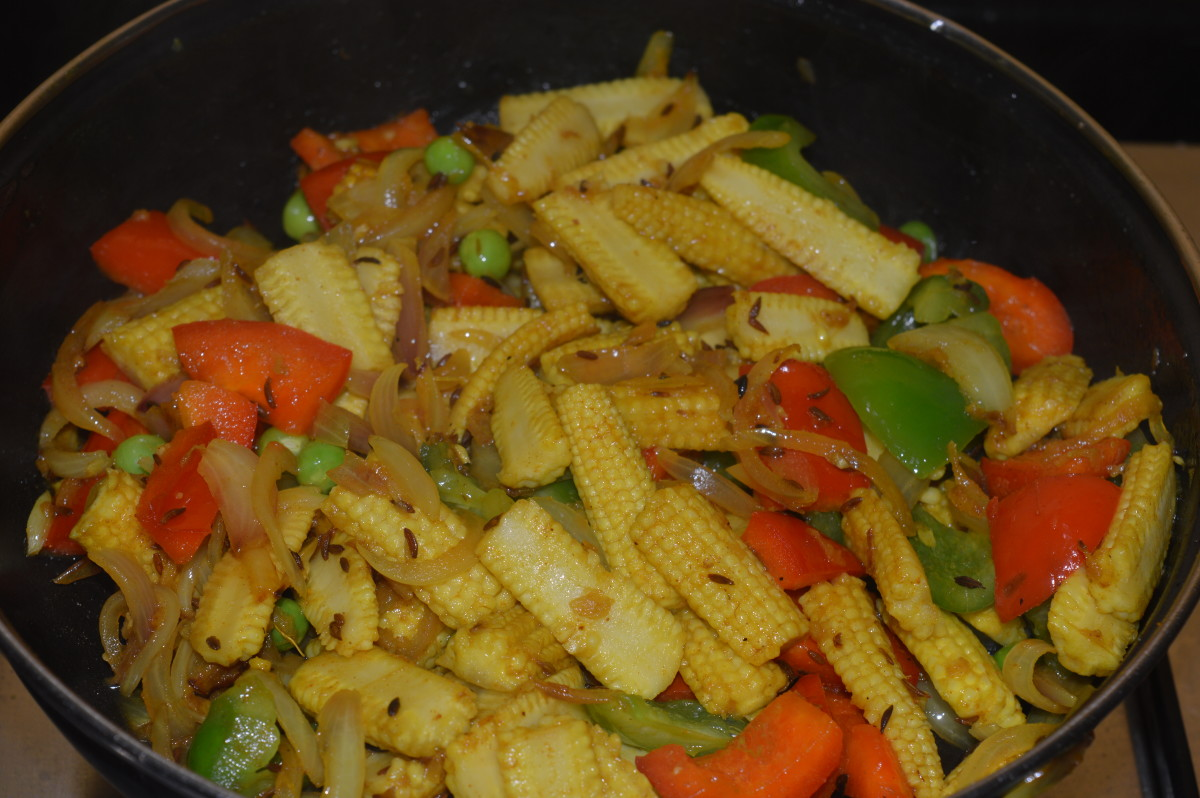 Step four: Add capsicum and par-boiled baby corn pieces. Continue stir-cooking for 5-6 minutes.