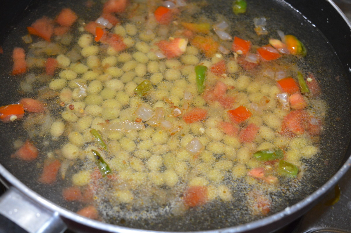 Step five: Add cooked hyacinth beans or green peas. Add 6 cups of water. Bring the mix to a boil. Add salt and sugar. Lower the heat.