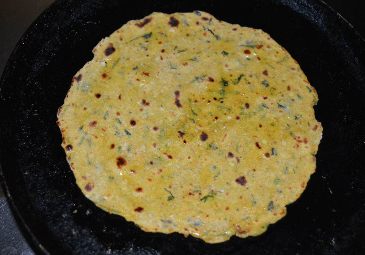 Step nine: Flip it when the bottom turns golden brown. Add a few drops of oil or ghee on the top. Cook the other side also till golden brown. Remove and place it on a plate. Make all the parathas like this.