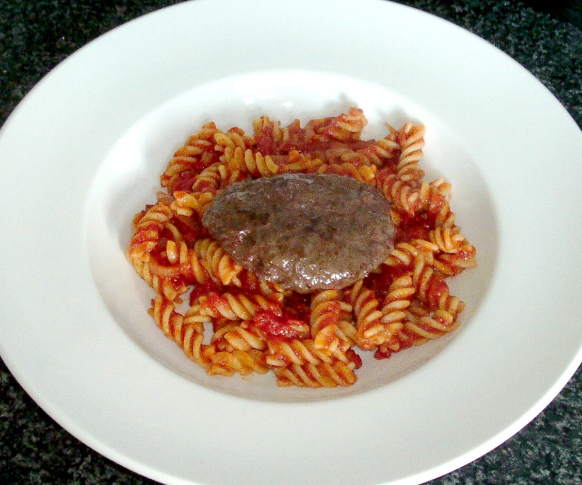 Buffalo and beef burger served on a bed of fusilli pasta in tomato sauce.