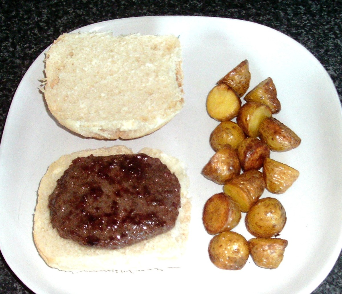 Burger and roast potatoes are plated