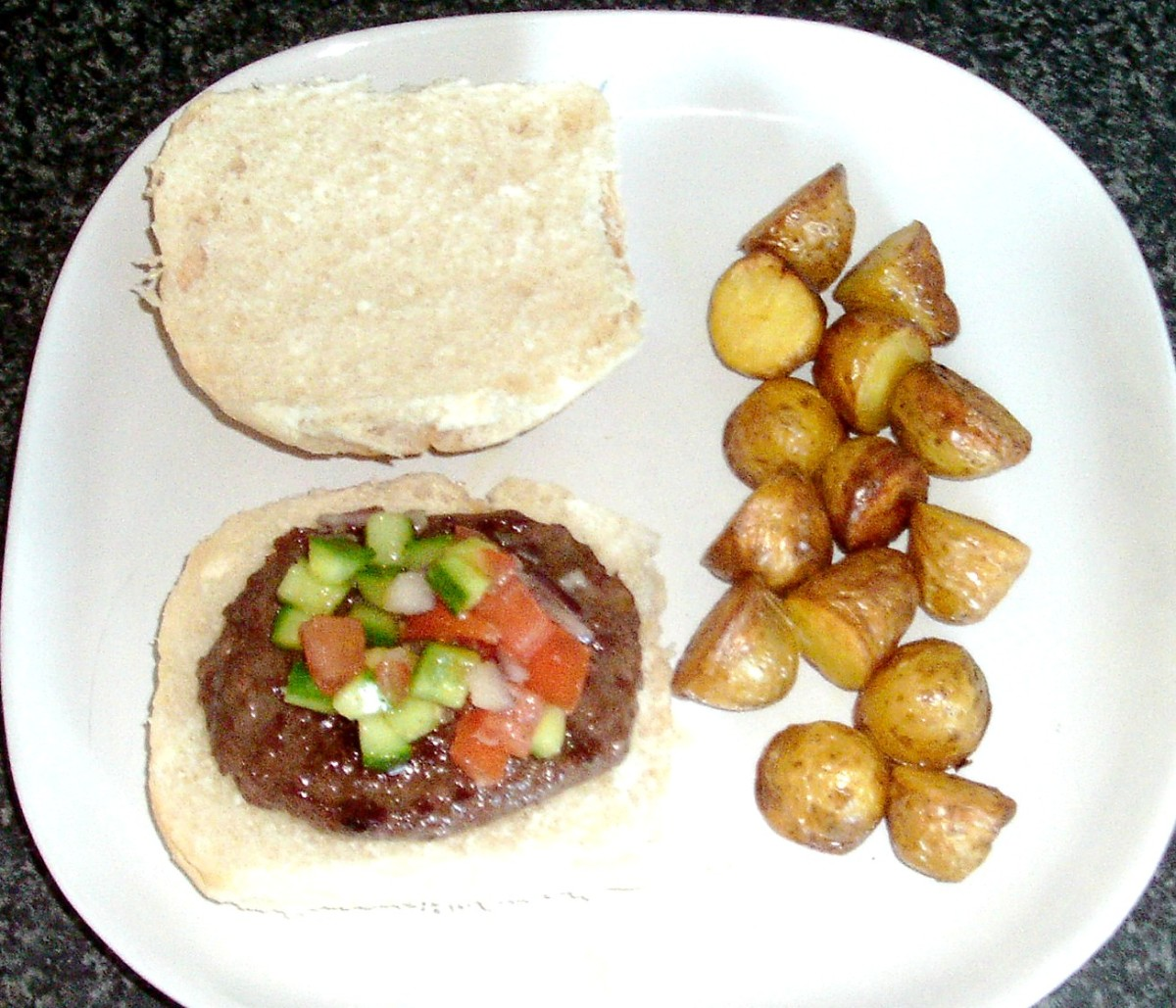 Buffalo and beef burger on a bread roll with spicy salsa and mini roast potatoes.
