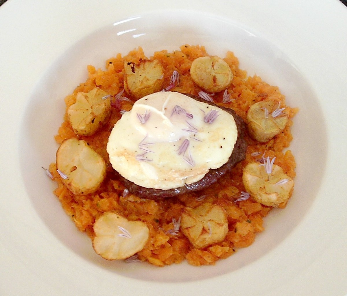 Buffalo and beef burger on carrot mash with deep-fried potato crowns, poached egg and chive flowers.
