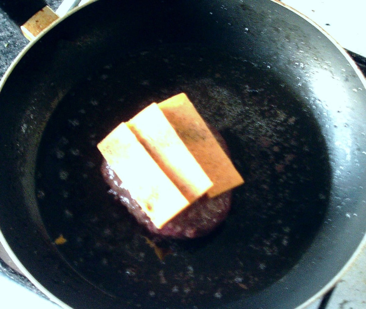 Cheese slices are laid on top of the cooked burger