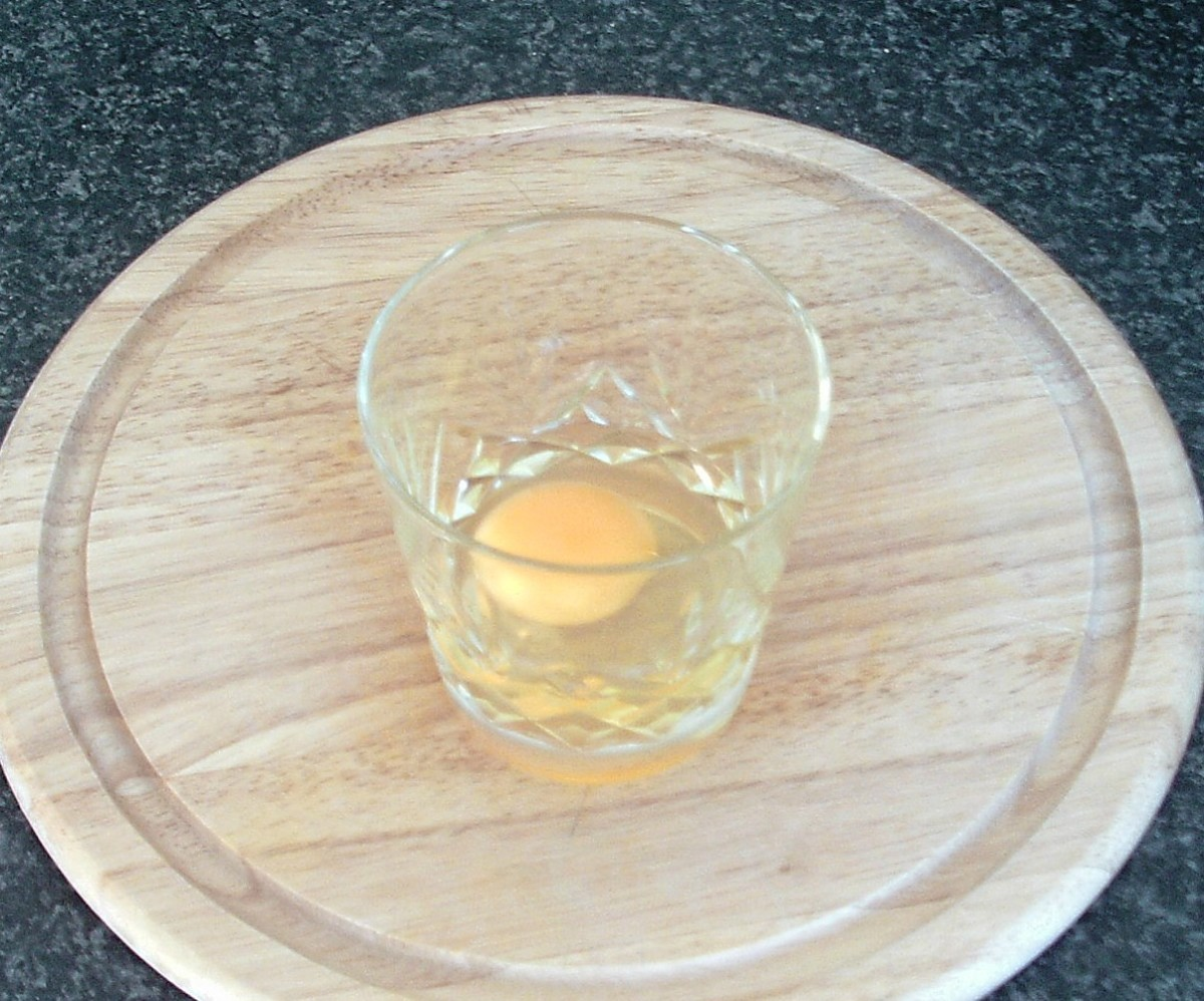 Egg is broken in to small glass or cup for adding to poaching water
