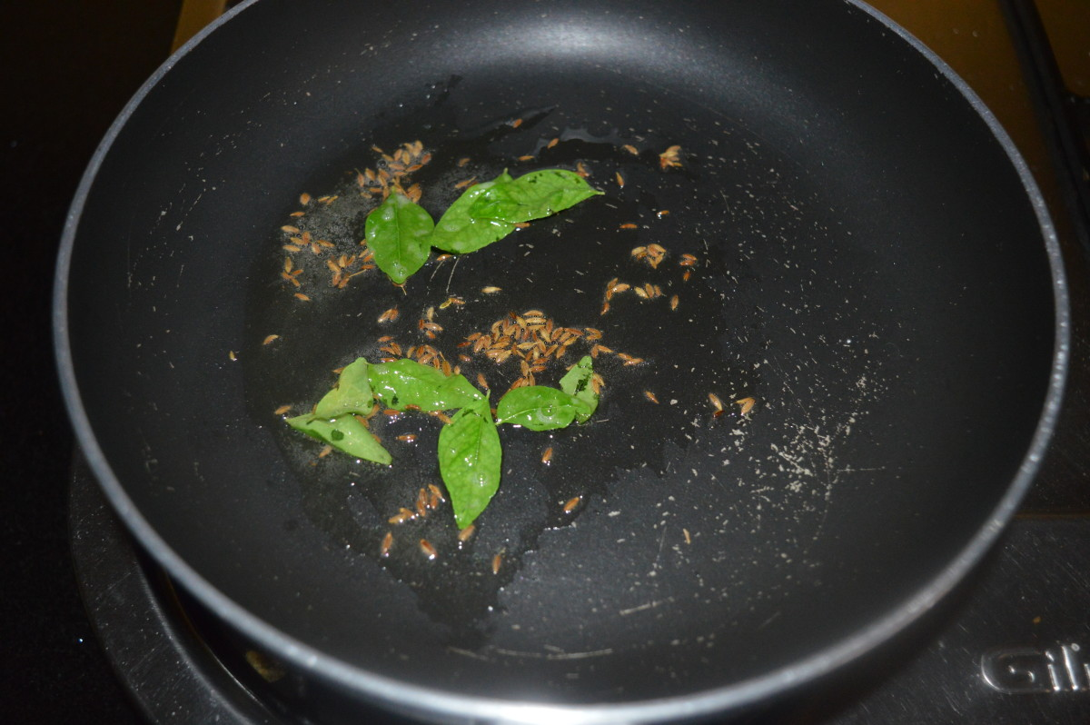Step five: Heat oil in a deep-bottomed pan. Add cumin seeds and curry leaves. Saute them till they sizzle.