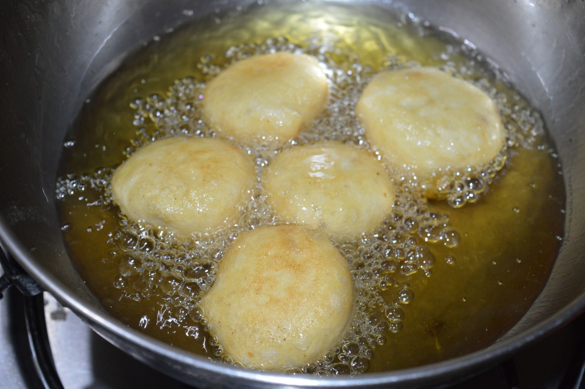 Step five: Heat oil for deep-frying. Take a lemon-sized batter in your fingers and drop it into the medium hot oil. Make 4-5 such dumplings at a time. Fry them till they are crispy and golden brown.