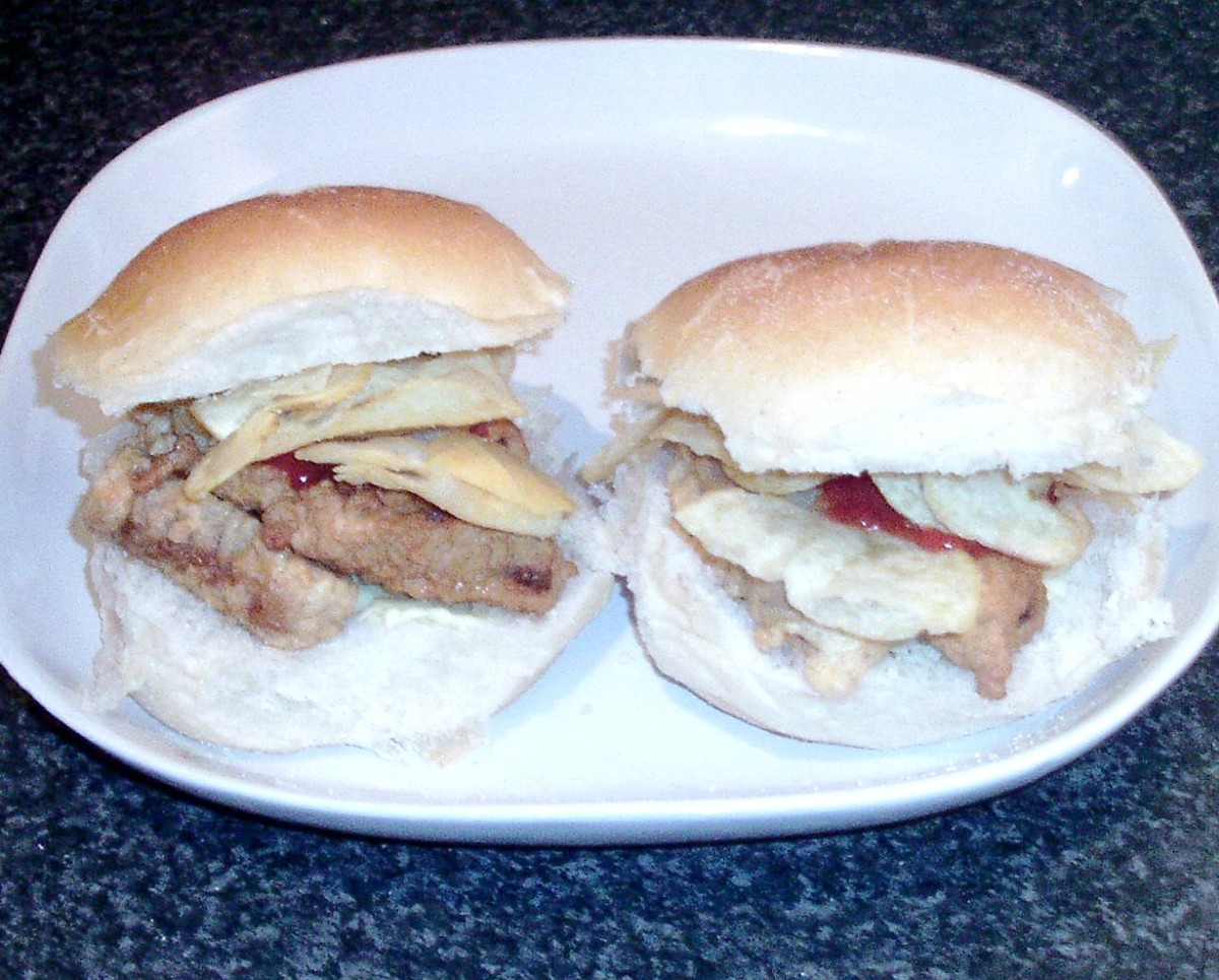 Deep fried sausages in batter with ketchup and salt and vinegar crisps on bread rolls